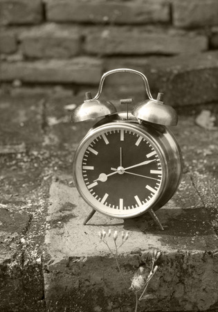 still life with vintage retro alarm clock on old brick background (black and white concept ) photo