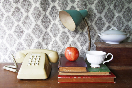 still life with old bookapple Push Button Telephonelamp and tea cop on wooden table. photo