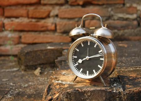 still life with vintage retro alarm clock on old brick background photo