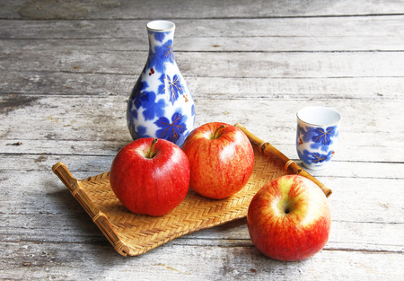 ceramic bottle: still life with ceramic bottle in bamboo tray basket and apple on wooden table.