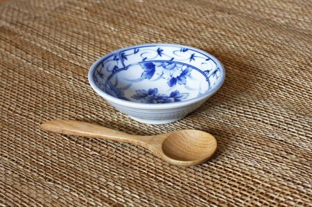 empty bowl: Empty bowl with spoon on bamboo mat. Stock Photo