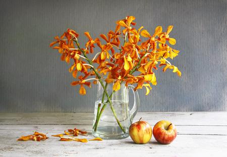 стиль жизни: натюрморт с кувшином орхидеи и яблока на деревянный стол. Фото со стока
