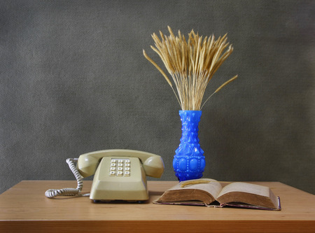 still life with Push Button Telephonevase of flowering grass and old book on wooden table. photo
