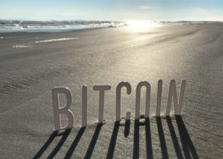Bitcoin word in Sand with Shadows by Sun