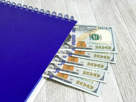Notepad with 100 dollar bills. Photo Image