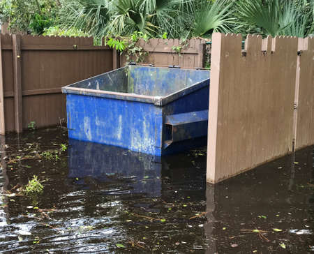 Dumpster cover by water flooding in hurricaine season. Photo image