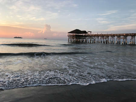 Sunset in Cocoa Beach Florida Pier with cruise ships in the horizon. Photo image