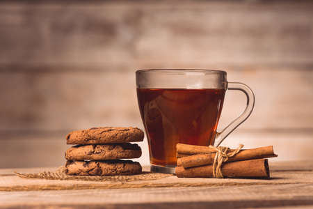 a cup with tea, cookies and cinnamon  on a wooden background