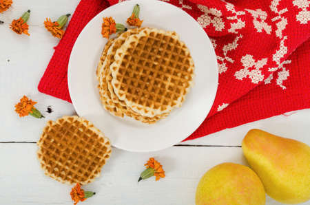 Waffles on a plate with pears and red cloth, top view Stock Photo