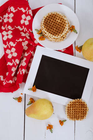 Wooden frame on the table with pears, waffles and red cloth, vertical view Stock Photo