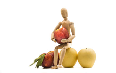 wooden man puppet sitting hugging a nectarine on white background Banco de Imagens - 81708026