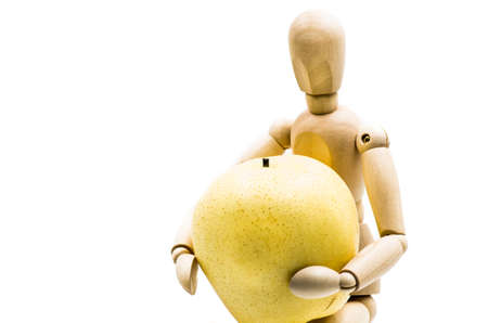 wooden man puppet sitting hugging a pear on white background Banco de Imagens - 81716626