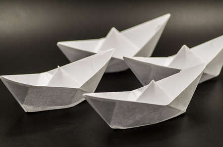 a fleet of white paper ships on black