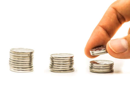 silver coins: piles of coins on white background with a hand putting extra coins Stock Photo