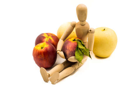 wooden man puppet sitting hugging a nectarine on white background Banco de Imagens - 81784622