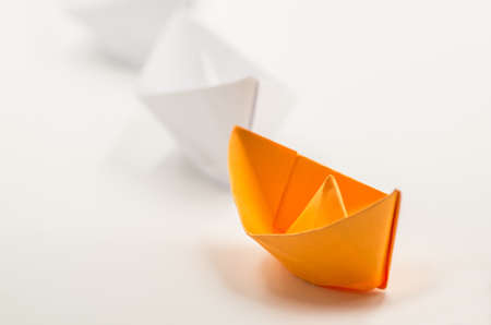 leader paper ship followed by other origami ships in a line