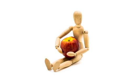 wooden man puppet sitting hugging a nectarine on white background Banco de Imagens - 81784636