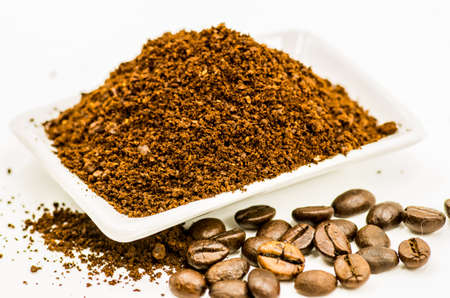 freshly grinded coffee beans on the white plate on white background Stock Photo