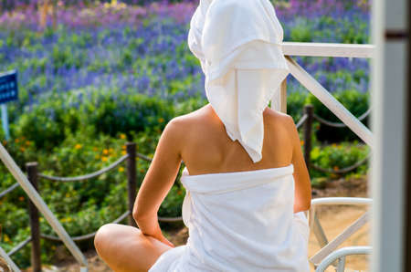 a woman in a bath towel is sitting on a lounge on a terrace looking ot the flowers