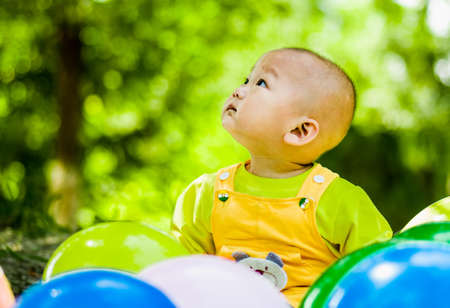 baby sits between balloons looking up