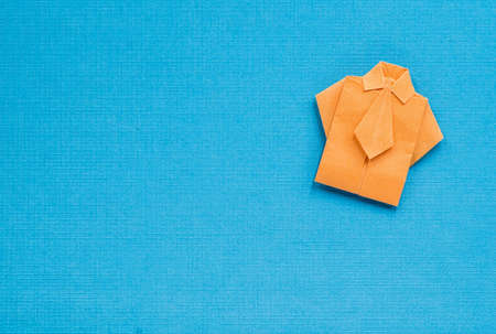 typical: origami orange paper shirt on textured blue background