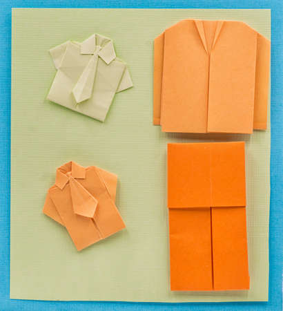 typical: origami paper man office suit on textured colorful background Stock Photo