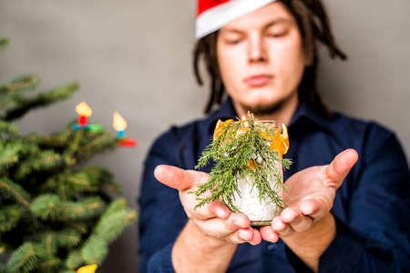 young european man in christmas hat with a candle and christmas tree on the background Imagens