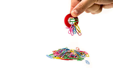 magnet covered with colorful paper clips in a hand of a man