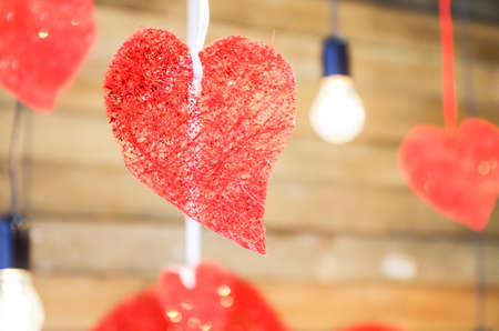 red heart hanging with lifht bulbs on wooden background