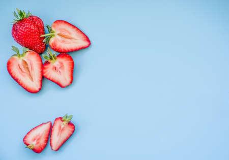 Fresas jugosas frescas sobre fondo azul.