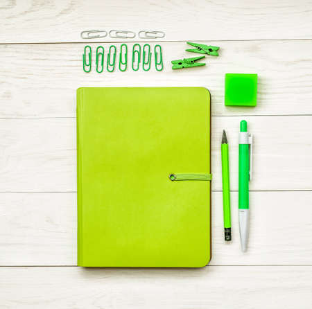 green notebook with eraser, pen,pencil and paper clips on white wooden background. creative set for dreawing,writing or making notes Imagens
