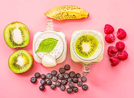 two banana and kiwi milkshakes in mason jars with creme on top decorated with kiwis, bananas, raspberries and blueberries. flat lay top view smoothie on pink