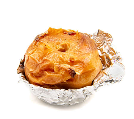 thanksgiving and christmas concept. Baked apple in aluminum foil isolated on white Stock Photo