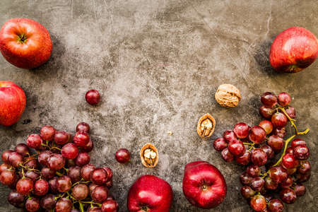 purple and red fruit: grapes, apples and walnuts top view on dark background flat lay. Healthy food or diet concept Stock Photo
