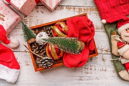 Christmas decorations in a wooden box on white rustic background