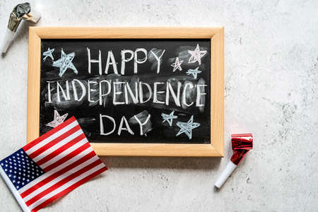 Independence Day USA concept. Memorial Day. Chalkboard with text Happy Independence Day decorated with noisemakers on USA flag