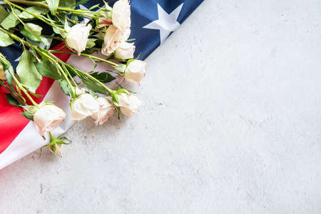 Independence Day USA concept. Memorial Day. White roses over the US flag top view