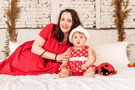 Happy mother with baby daughter lying on white bed at home