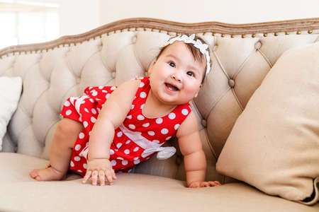 cute asian baby girl in red dress playing on the beige sofa