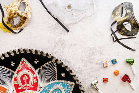 Carnival or party concept. Sombrero, noisemakers, small gifts and masks top view flat lay