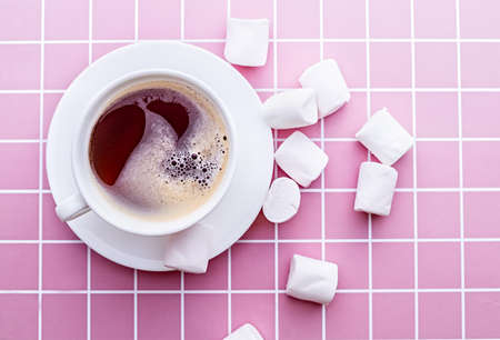 Coffee with marshmallows in a white Cup on pink background top view flat lay