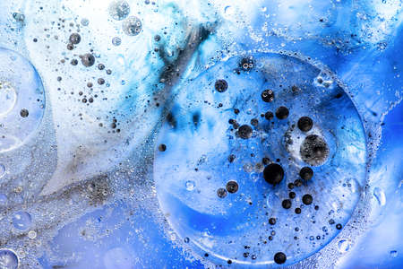 Abstract background. Bright blue bubbles with black ink on water surface