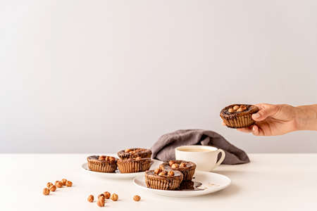 chocolate cupcakes with glazing, walnuts and a cup of coffee on white table front view Imagens