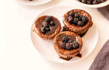 fresh homemade muffins decorated with chocolate topping and blackberries on white plate