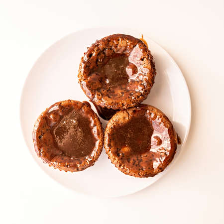 fresh homemade chocolate muffins with topping on white plate top view Imagens