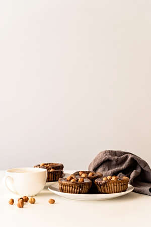 Homemade chocolate cupcakes with glazing, walnuts and a cup of coffee on white table front view