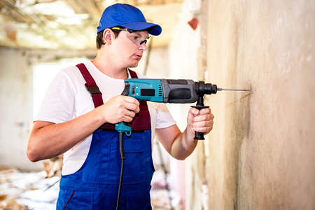 Construction worker in protection glasses and uniform with perforator drilling the wall indoors. Man with drill