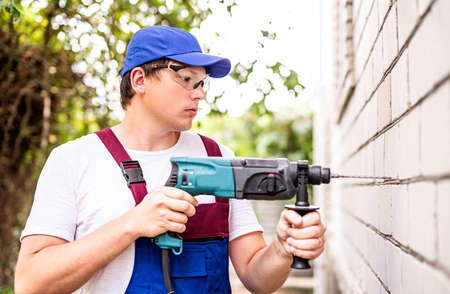 Construction worker in protection glasses and uniform with perforator drilling the wall outdoors. Man with drill Imagens