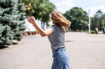 True happiness concept. Happy young caucasian woman with long hair turning around having fun in the park Archivio Fotografico