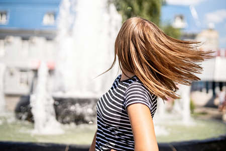 True happiness concept. Young caucasian woman in casual clothes shaking her hair on urban fountain background